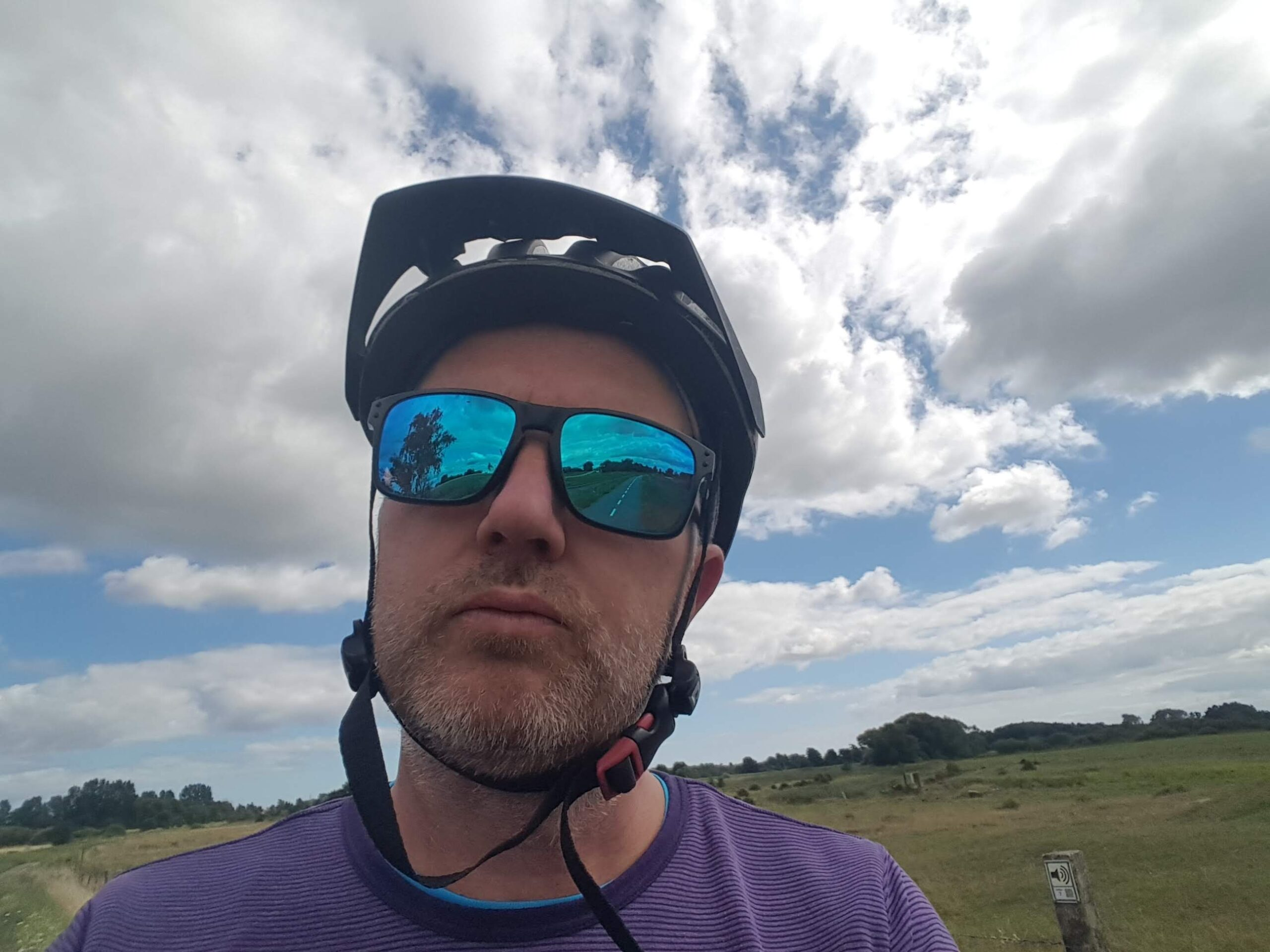 An image of a cyclist waeting mirrorshades and a helmet.